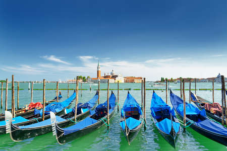 lagoon: A row of gondolas parked beside the Riva degli Schiavoni in Venice, Italy. Scenic view the Venetian Lagoon at summer time. The Church of San Giorgio Maggiore on island is visible in background.