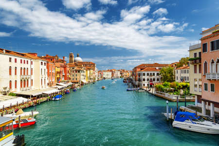 Beautiful view of the Grand Canal with boats from the Ponte degli Scalzi in Venice, Italy. Colorful facades of old houses on waterfront. Venice is a popular tourist destination of Europe.