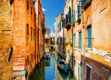 italy street: Beautiful view of the Rio Terra Secondo Canal from street Calle Seconda del Cristo in Venice, Italy. Colorful facades of old medieval houses. Venice is a popular tourist destination of Europe. Stock Photo