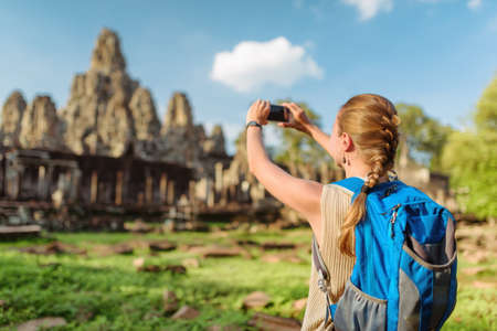 siem reap: Young female tourist with backpack and smartphone taking picture of ancient Bayon temple in Angkor Thom on blue sky background in evening sun. Siem Reap, Cambodia.