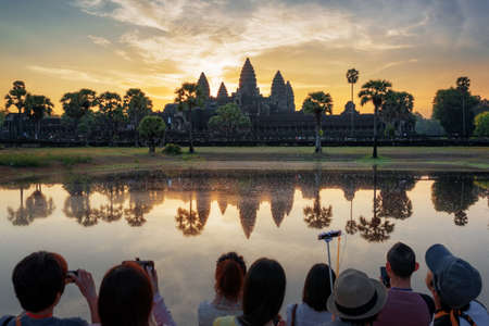 take a history: Many Asian tourists taking picture of ancient temple Angkor Wat at sunrise. Siem Reap, Cambodia. Towers of Angkor Wat reflected in lake at dawn. Angkor Wat is a popular tourist attraction.