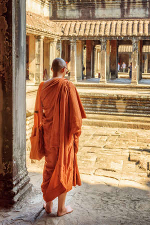 buddhist monk: Buddhist monk exploring courtyards of ancient temple complex Angkor Wat in Siem Reap, Cambodia. Mysterious Angkor Wat is a popular destination of tourists and pilgrims.