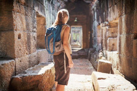 Young female tourist with blue backpack exploring mysterious ruins of ancient Preah Khan temple in Angkor. Siem Reap, Cambodia. Toned image. Stock Photo