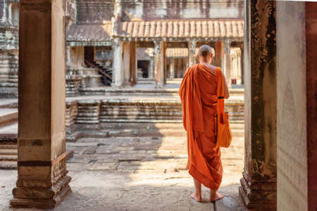 buddhist monk: Buddhist monk exploring ancient courtyards of temple complex Angkor Wat in Siem Reap, Cambodia. Amazing Angkor Wat is a popular destination of tourists and pilgrims. Stock Photo