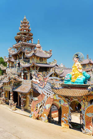 lat: Side view of the Linh Phuoc Pagoda in the mosaic style from shards of glass, pottery and porcelain on the blue sky background in Da Lat city, Vietnam. Da Lat is a popular tourist destination of Asia.