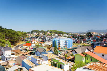 lat: Many colorful houses of Da Lat city (Dalat) on the blue sky background in Vietnam. Da Lat and the surrounding area is a popular tourist destination of Asia. Stock Photo
