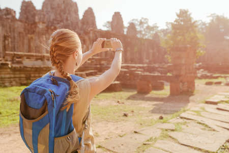 take a history: Young female tourist with blue backpack and smartphone taking picture among mysterious ruins of ancient Angkor Thom in Siem Reap, Cambodia. Toned image. Stock Photo