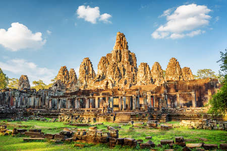 bayon: Main view of ancient Bayon temple in Angkor Thom in evening sun. Mysterious Angkor Thom nestled among rainforest in Siem Reap, Cambodia. Enigmatic Angkor Thom is a popular tourist attraction.