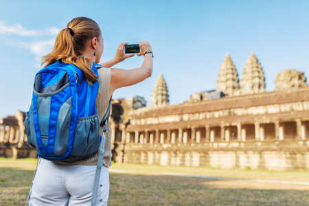 take a history: Young female tourist with blue backpack and smartphone taking picture of the eastern facade of the ancient mysterious temple complex Angkor Wat on blue sky background. Siem Reap, Cambodia.