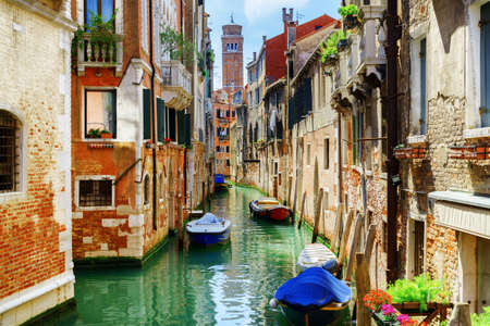 The Rio di San Cassiano Canal with boats and colorful facades of old medieval houses in Venice, Italy. Bell-tower of San Cassiano (Church of Saint Cassian) is visible in background.