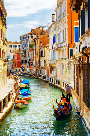 marin: Tourists traveling in gondola. View of the Rio Marin Canal with boats from the Ponte de la Bergami in Venice, Italy. Venice is a popular tourist destination of Europe.