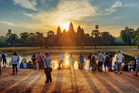 take a history: Tourists taking picture of ancient temple complex Angkor Wat at sunrise. The sun reflected in lake at dawn. Mysterious Angkor Wat is a popular tourist attraction.