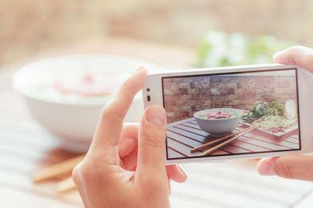 Vista del primo piano di processo lifeview su uno smartphone per scattare una foto di Pho Bo in caffè della via in Vietnam. Il Pho Bo è un tradizionale zuppa di noodle manzo vietnamita. Popolare cibo di strada sano. Archivio Fotografico