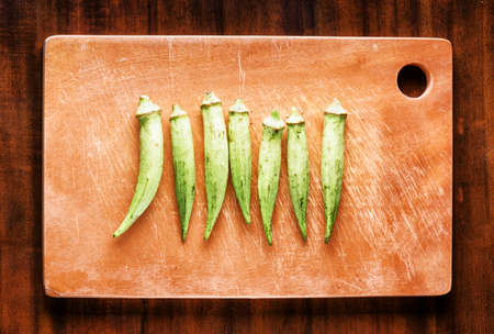 folate: Fresh green seed pods okra on wooden board on a table. Healthy eco food rich in vitamins, folate, antioxidants, calcium and potassium. Popular product of organic farming in Asia.
