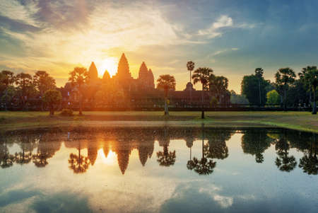 sunrise: Towers of ancient temple complex Angkor Wat at sunrise. Siem Reap, Cambodia. Temple Mountain and the sun reflected in lake at dawn. Mysterious Angkor Wat is a popular tourist attraction.