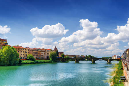 trinita: View of the Ponte alla Carraia over the Arno River in Florence, Tuscany, Italy. Dome of the Church of Saint Fridianus (San Frediano in Cestello) is visible in background.