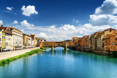 destination scenic: Scenic view of medieval stone bridge Ponte Vecchio (Old Bridge) and the Arno River from the Ponte Santa Trinita in Florence, Tuscany, Italy. Florence is a popular tourist destination of Europe.