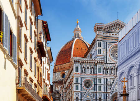 saint: The Cathedral of Saint Mary of the Flower (Florence Cathedral) at historic center of Florence, Tuscany, Italy. View from the Piazza San Giovanni. Dome on blue sky background.