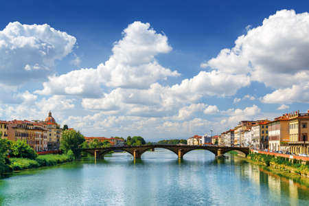 trinita: The Ponte alla Carraia over the Arno River in Florence, Tuscany, Italy. View from the Ponte Santa Trinita Holy Trinity Bridge. Florence is a popular tourist destination of Europe.