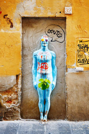 italy street: FLORENCE, ITALY - AUGUST 25, 2014: Street art at historic center of Florence, Tuscany, Italy. Modern painted sculpture in niche of old building on medieval street. Editorial
