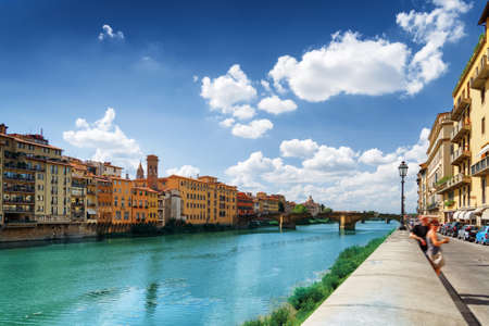 trinita: View of the Ponte Santa Trinita Holy Trinity Bridge from the Lungarno degli Archibusieri in Florence, Tuscany, Italy. Facades of old medieval houses on waterfront of the Arno River. Stock Photo