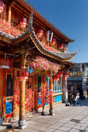 old town house: DALI, YUNNAN PROVINCE, CHINA - OCTOBER 21, 2015: Wooden facade of traditional Chinese house decorated with flowers and red lanterns in Dali Old Town. The ancient city is a popular tourist destination. Editorial