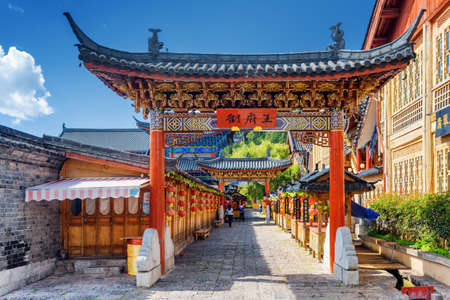 old street: LIJIANG, YUNNAN PROVINCE, CHINA - OCTOBER 23, 2015: Traditional Chinese wooden gate on street in the Old Town of Lijiang. The Old Town of Lijiang is a popular tourist destination of Asia.