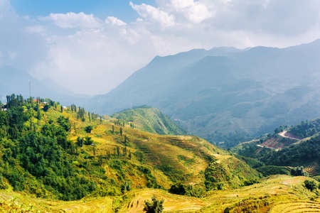lien: Sunlit rice terraces at highlands of Sapa District, Lao Cai Province, Vietnam. The Hoang Lien Mountains and cloudy sky in background. Sa Pa is a popular tourist destination of Asia. Stock Photo