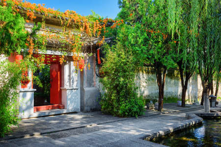 old town house: Red doors leading into courtyard of traditional Chinese house in Dali Old Town, Yunnan province, China. Beautiful view of street with flowers and green trees at the ancient city. Stock Photo