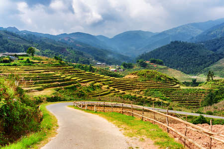 lien: Bending road among rice terraces in the Hoang Lien Mountains of Sapa District, Lao Cai Province, Vietnam. Sa Pa is a popular tourist destination of Asia. Dramatic sky in background. Stock Photo