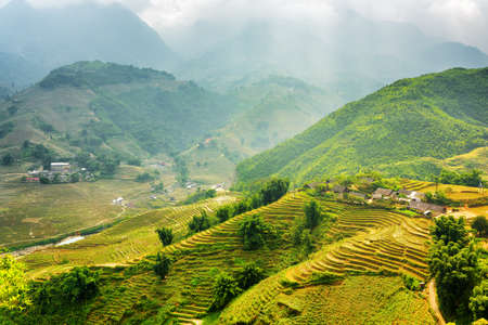lao: Scenic view of rays of sunlight illuminating rice terraces through storm clouds at highlands of Sapa District, Lao Cai Province, Vietnam. Sa Pa is a popular tourist destination of Asia.
