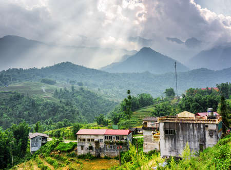 lien: Scenic view of old houses at highlands of Sapa District, Lao Cai Province, Vietnam. Rays of sunlight through stormy clouds in the Hoang Lien Mountains are visible in background.