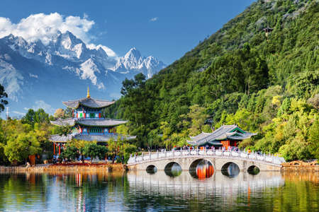 Beautiful view of the Jade Dragon Snow Mountain and the Black Dragon Pool, Lijiang, Yunnan province, China. The Suocui Bridge over pond and the Moon Embracing Pavilion in the Jade Spring Park.