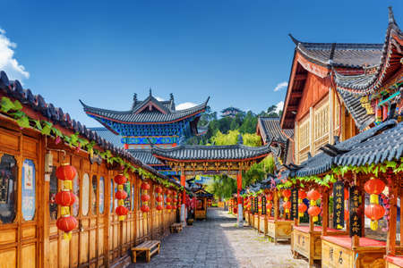 LIJIANG, YUNNAN PROVINCE, CHINA - OCTOBER 23, 2015: Scenic street decorated with traditional Chinese red lanterns in the Old Town of Lijiang. Lijiang is a popular tourist destination of Asia. Zdjęcie Seryjne - 50972728