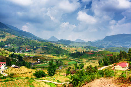 lao: View of village and terraced rice fields at highlands of Sapa District, Lao Cai Province, Vietnam. Sa Pa is a popular tourist destination of Asia. Dramatic stormy sky in background.