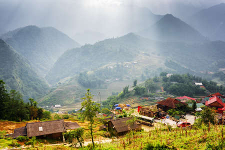 lien: Scenic view of Cat Cat Village at highlands of Sapa District, Lao Cai Province, Vietnam. Rays of sunlight through stormy clouds in the Hoang Lien Mountains are visible in background. Stock Photo