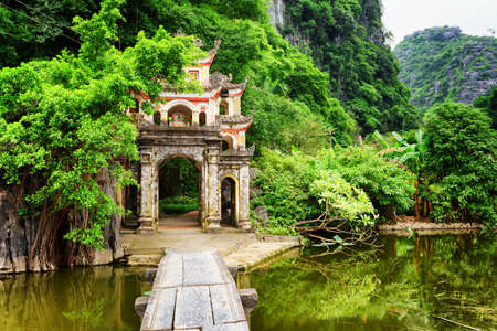main gate: Scenic view of main gate to the Bich Dong Pagoda, Ninh Binh Province, Vietnam. Stone bridge over lake leading to ancient Buddhist temple. The Bich Dong Pagoda is a popular tourist destination of Asia.