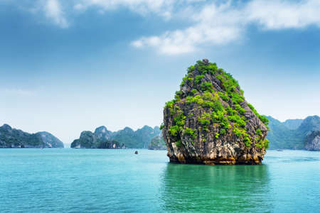 destination scenic: Scenic view of karst isle on blue sky background in the Ha Long Bay (Descending Dragon) at the Gulf of Tonkin of the South China Sea, Vietnam. The Halong Bay is a popular tourist destination of Asia.