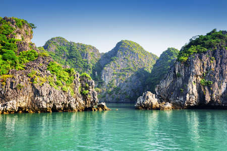 karst: Scenic view of azure water and karst islands on blue sky background in the Ha Long Bay at the Gulf of Tonkin of the South China Sea, Vietnam. The Halong Bay is a popular tourist destination of Asia.