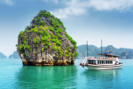 Beautiful view of karst isle and tourist boat in the Ha Long Bay (Descending Dragon Bay) at the Gulf of Tonkin of the South China Sea, Vietnam. The Halong Bay is a popular tourist destination of Asia