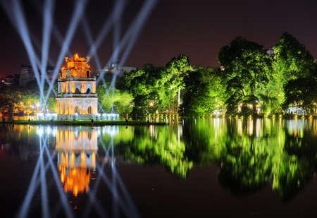 ホアン キエム湖 (返される剣の湖) とベトナムのハノイの歴史的中心部で青い光線間タートル タワーの夜景。タワーは湖に映った。