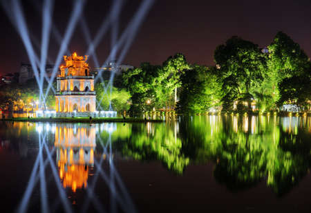 Night view of the Hoan Kiem Lake (Lake of the Returned Sword) and the Turtle Tower among blue light rays at historic centre of Hanoi in Vietnam. The tower reflected in the lake. Stock Photo