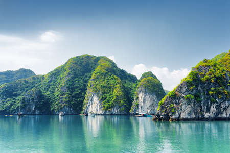 halong: Beautiful azure water of lagoon in the Halong Bay (Descending Dragon Bay) at the Gulf of Tonkin, the South China Sea, Vietnam. Scenic landscape formed by karst towers-isles on blue sky background. Stock Photo
