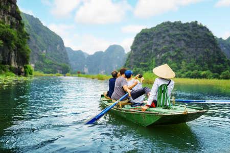 Los turistas que viajan en barco por el río Ngo Dong y toman el cuadro del Tam Coc, Ninh Binh, Vietnam. Remero usando sus pies para propulsar remos. Paisaje formado por torres de piedra caliza y campos de arroz.