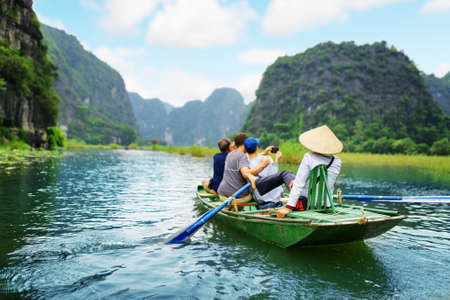 culture: Tourists traveling in boat along the Ngo Dong River and taking picture of the Tam Coc, Ninh Binh, Vietnam. Rower using her feet to propel oars. Landscape formed by karst towers and rice fields.