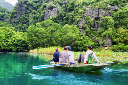 ngo: Tourists traveling in small boat along the Ngo Dong River at the Tam Coc portion, Ninh Binh Province, Vietnam. Rower using her feet to propel oars. Beautiful landscape formed by karst towers. Stock Photo