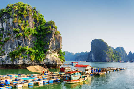 the bay: Floating fishing village in the Halong Bay (Descending Dragon) at the Gulf of Tonkin of the South China Sea, Vietnam. Landscape formed by karst towers-isles in various sizes. Blue sky in background. Stock Photo