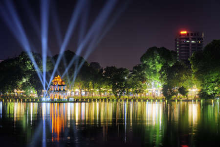 returned: Night view of the Hoan Kiem Lake (Lake of the Returned Sword) and the Turtle Tower among blue light rays at historic centre of Hanoi, Vietnam. The Hoan Kiem Lake is a popular tourist destination. Stock Photo