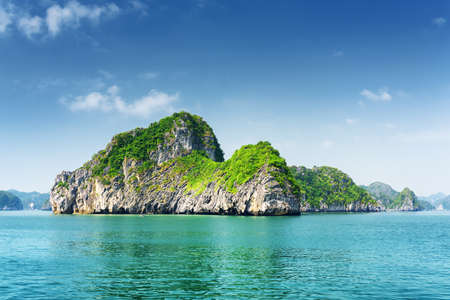 destination scenic: Scenic view of karst rocks-isles and azure water in the Ha Long Bay (Descending Dragon) at the Gulf of Tonkin of the South China Sea, Vietnam. The Halong Bay is a popular tourist destination of Asia.
