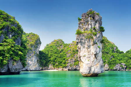 Amazing view of rock pillar and azure water in the Ha Long Bay (Descending Dragon Bay) at the Gulf of Tonkin of the South China Sea, Vietnam. The Halong Bay is a popular tourist destination of Asia.